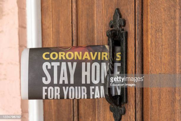 Newspaper delivery with Government message Coronavirus Stay Home issue into a letterbox of home Hampshire UK