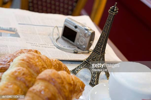 Newspaper, digital camera, Eiffel Tower souvenir and croissants on table