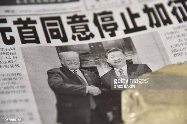 A newspaper featuring a front page story about the meeting between US President Donald Trump and Chinese President Xi Jinping as seen at a news stand...