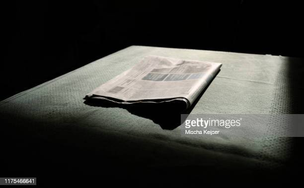 a newspaper folded, waiting to be read in morning light, low key - news not politics stock pictures, royalty-free photos & images