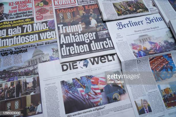Newspaper front pages show yesterday's storming by supporters of U.S. President Donald Trump of the U.S. Capitol on January 7, 2021 in Berlin,...