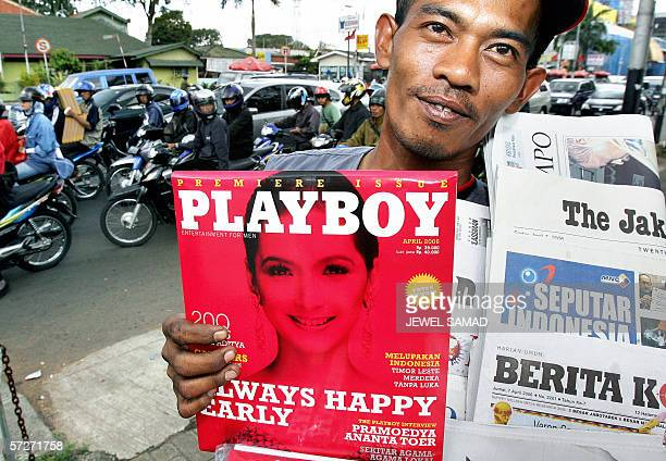 A newspaper hawker displays a copy of the first edition of Indonesian version Playboy magazine along with other newspapers and magazines while...