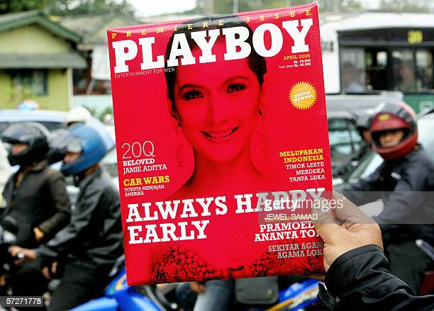 A newspaper hawker displays a copy of the first edition of Indonesian version Playboy magazine while looking for customers along a street in downtown...