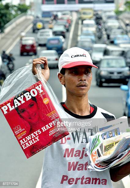 A newspaper hawker displays a copy of the first edition of the Indonesian version Playboy magazine along with other newspapers and magazines while...