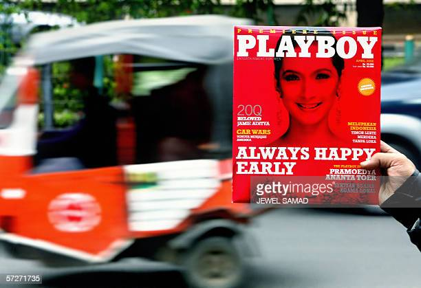 A newspaper hawker displays a copy of the first edition of the Indonesian version Playboy magazine while looking for customers along a street in...
