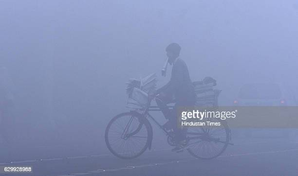 A newspaper hawker rides his bicycle in foggy weather on December 15 2016 in Amritsar India India will witness 'above normal' winter this year but...