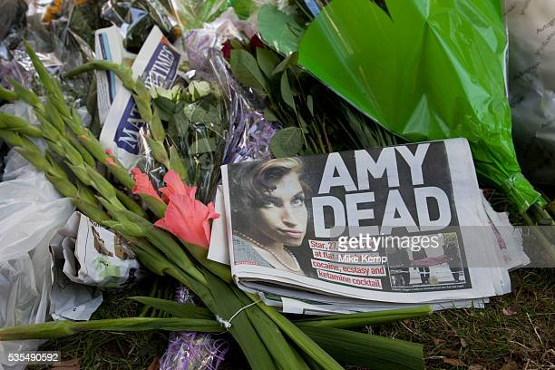 A newspaper headline reads 'AMY DEAD' as people gather and lay flowers at a memorial opposite the home of Amy Winehouse Camden Square North London It...