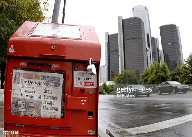 """Newspaper headline reads """"Sides Hammer Out Two Tier Wage Deal"""" at a box outside of the General Motors world headquarters building after the United..."""