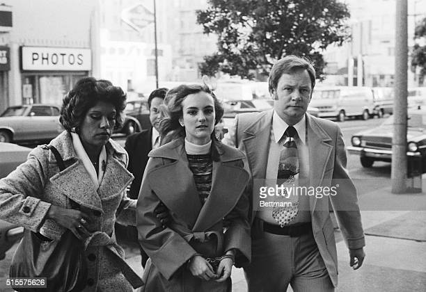 Newspaper heiress, Patty Hearst, is led to her 1976 trial by two federal marshals.