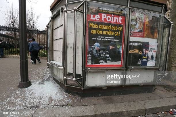 A newspaper kiosk with windows broken by demonstrators shows yhe cover of a French magazine reading quot But when will we stop this quot during an...