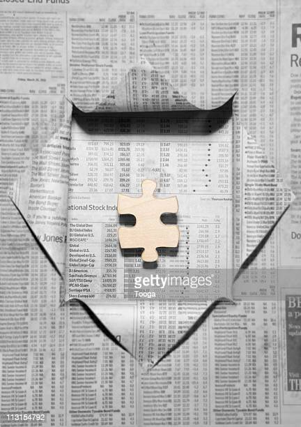 Newspaper of financials revealing puzzle piece