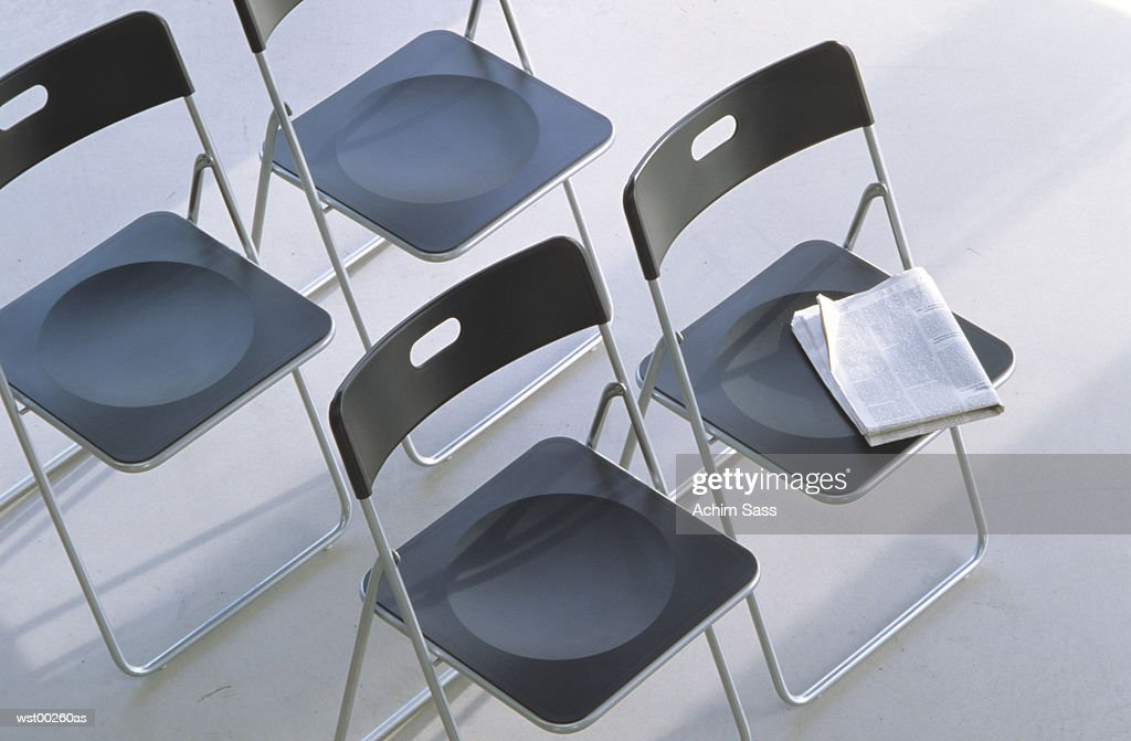 Newspaper on one of four fold up chairs : Stock Photo