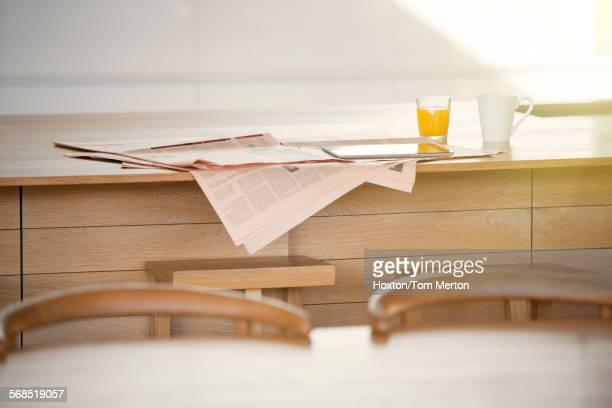 Newspaper, orange juice and coffee on kitchen island