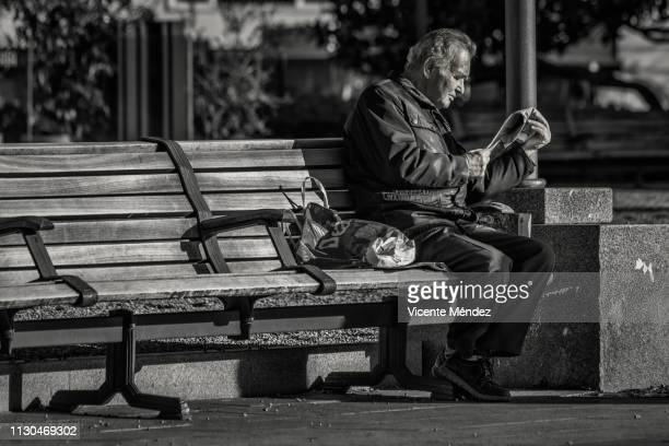 newspaper reader on a bench - vicente méndez fotografías e imágenes de stock