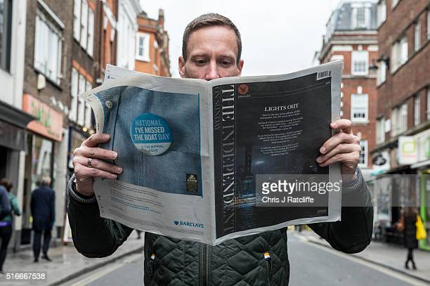 A newspaper reader reads the last ever print edition of The Independent On Sunday on the street in Soho on March 20 2016 in London England The...