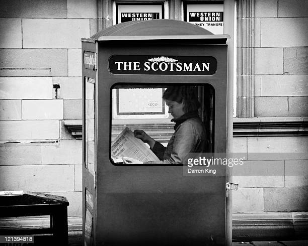 Newspaper saleswoman sits inside a Scotsman sales box on Edinburgh's George Street, reading a copy of the newspaper. The image is black and white.