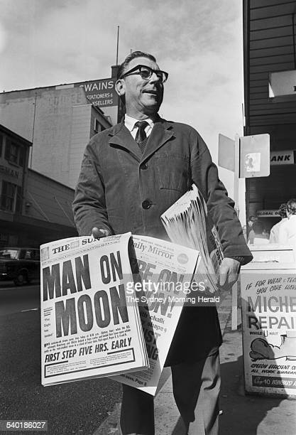 A newspaper seller hawks headlines 'Man on the Moon' as American astronaut Neil Armstrong becomes the first man to walk on the moon broadcast on...