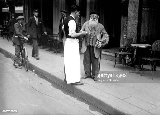 Newspaper seller in the street circa 1920 in Paris France
