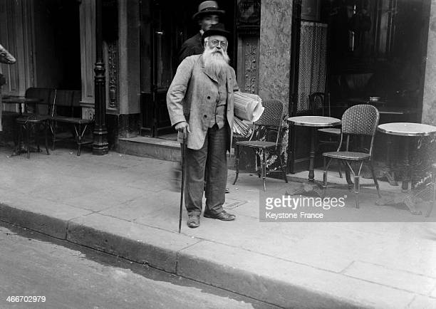 Newspaper seller strolling along the streets and waiting for customers circa 1920 in Paris France