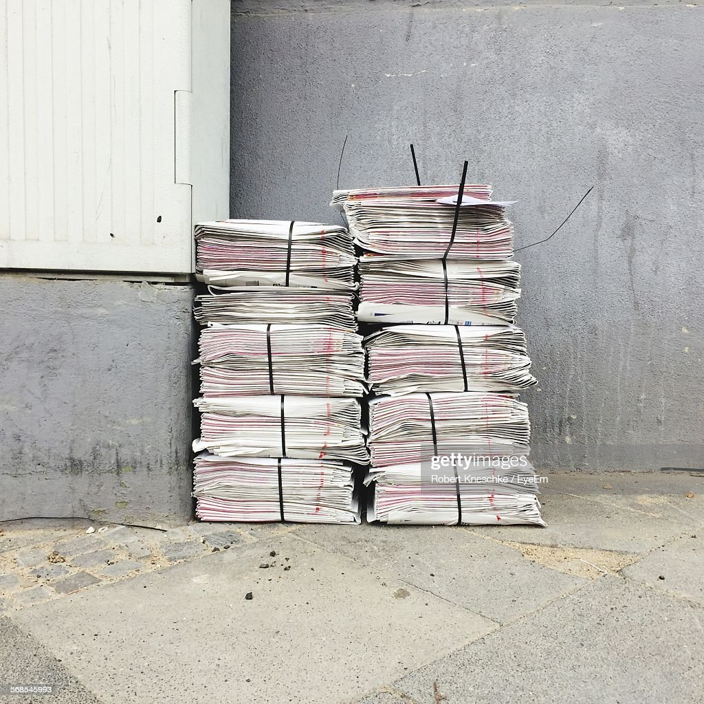 Newspaper Stacks Against Wall : Stock Photo