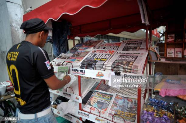 A newspaper vendor arranges local papers which front pages show pictures of Panama's former dictator Manuel Noriega in Panama City on December 12...