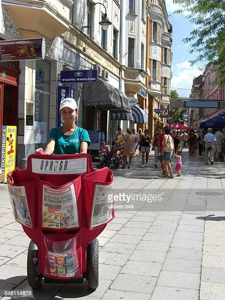 newspaper vendor driving a Segway in the pedestrian area