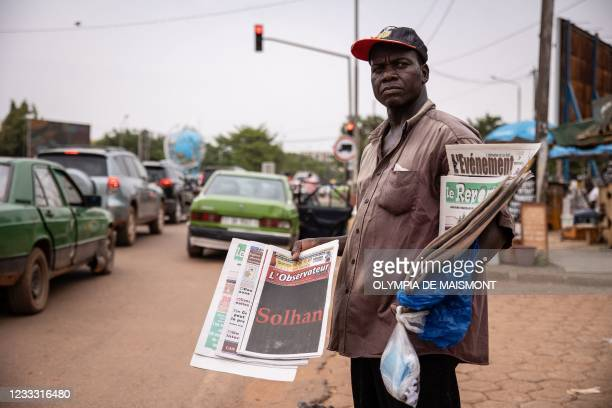 Newspaper vendor holds the L'Observateur Paalga newspaper with Solhan written on the front page, in Ouagadougou on June 7, 2021. - Suspected...
