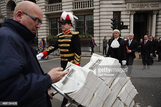 A newspaper vendor looks at his phone as Colonel Geoffrey Godbold walks past from Mansion House to the Royal Exchange to read the proclamation for...