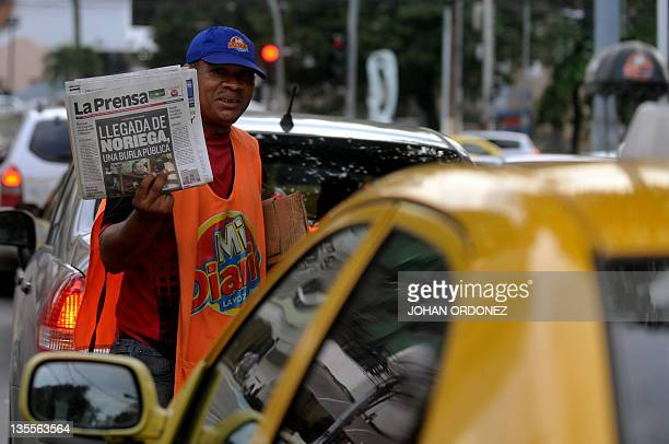 A newspaper vendor offers local papers which front page shows the picture of Panama's former dictator Manuel Noriega in Panama City on December 12...