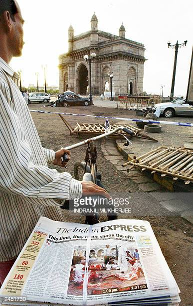 Newspaper vendor Rajesh Chawal pauses during his round to have a look at the bomb blast site at the historic Gateway of India in Bombay early...