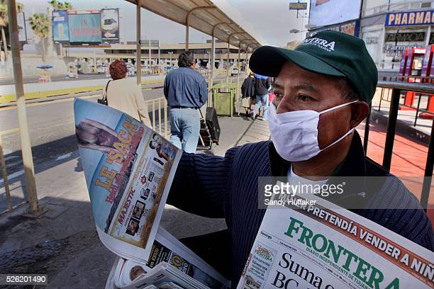 A newspaper vendor sells papers along the MexicoUnited States border crossing wearing a surgical mask at the Port of entry on Sunday May 3 2009The...