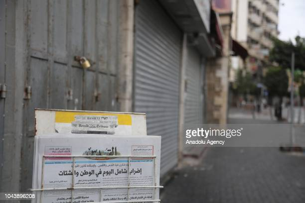 Newspapers are seen in front of a closed shop with a lock on its door in Ramallah, West Bank on October 01, 2018 during a general strike to protest...