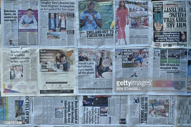 Newspapers, including articles about COVID-19, are pasted on the window of a disused shop in the High Sreet of Royal Tunbridge Wells, south west...