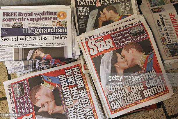 Newspapers lying at a newsstand show their Royal Highnesses Prince William, Duke of Cambridge and Catherine, Duchess of Cambridge kissing following...