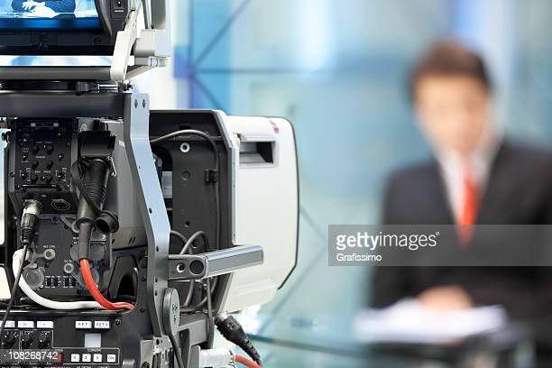 Newsreader in front of television camera