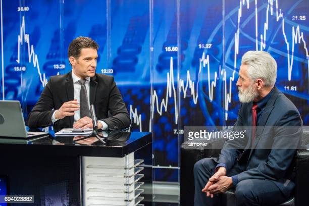 Newsreader sitting with businessman