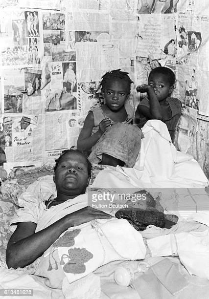 Newssheets paper the walls of a shanty home where a father lies in bed surrounded by his children
