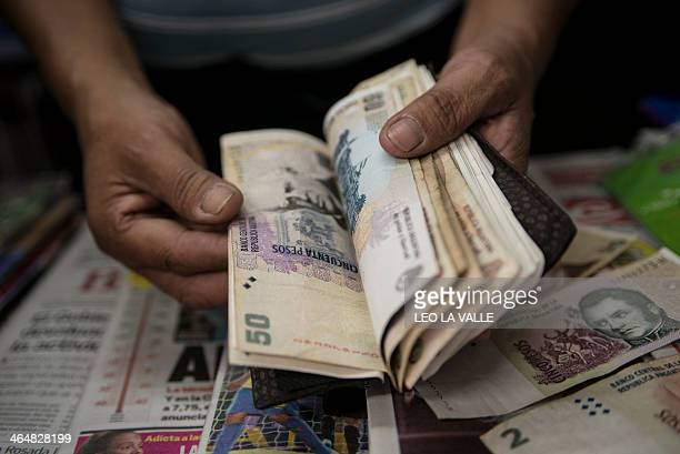 A newsstand owner counts Argentine pesos bills in Buenos Aires on January 24 2014 Argentina on Friday lifted restrictions in place since 2011 that...