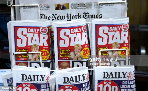 A newsstand rack in London England features daily newspapers including The New York Times from the US and the Daily Star and the Daily Express both...