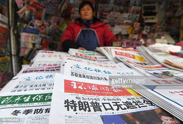 A newsstand vendor stands behind newspapers including one with a headline story about US Presidentelect Donald Trump in Beijing on December 6 2016...