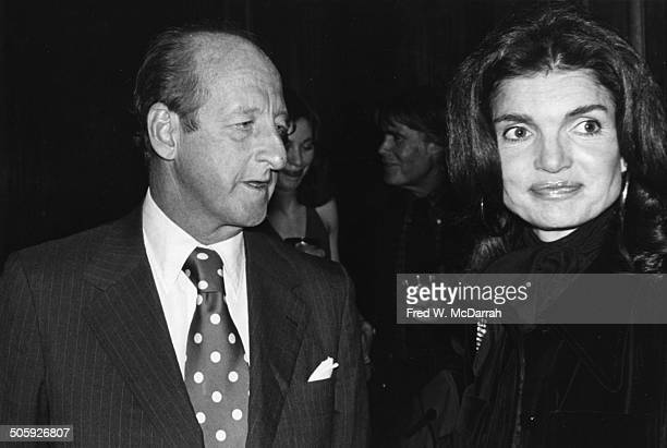 Newsweek editor Osborn Elliott talks with former First Lady Jacqueline Kennedy Onassis at the inaugural exhibit of the International Center of...