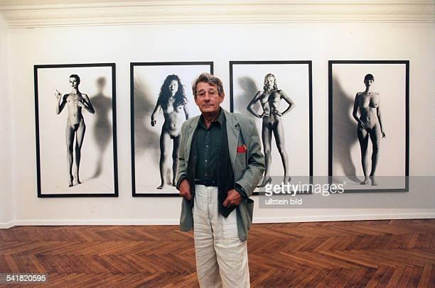 Newton Helmut *Fotograf Australien Halbportrait vor Fotos seiner Ausstellung 'Big Nudes' 1995