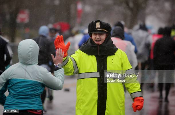 Newton Police Lt Bruce Apotheker right encourages runners on Heartbreak Hill during the Boston Marathon in Newton Mass April 16 2018