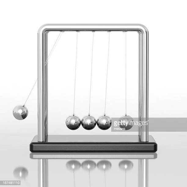 Newton's cradle sitting on a reflective desk