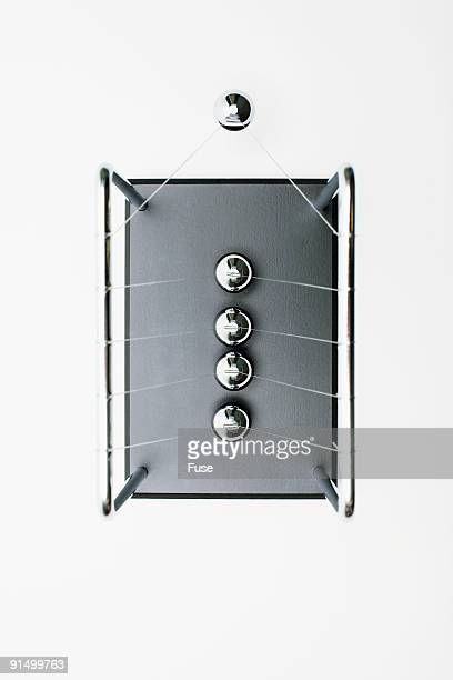 newton's cradle swinging - desk toy stock photos and pictures