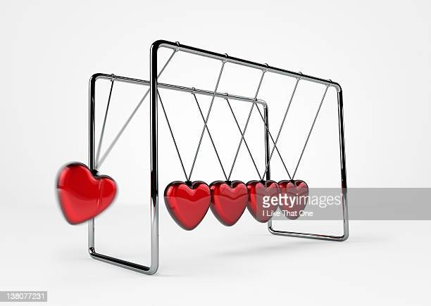 Newton's Cradle with hearts hanging from it