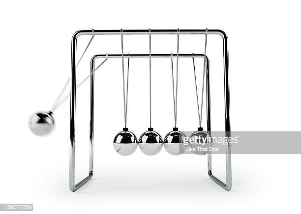 newton's cradle with one ball falling to group - desk toy stock photos and pictures