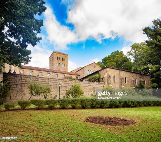 new-york city the cloisters museum with lawn and partly cloudy sky - cloister stock pictures, royalty-free photos & images