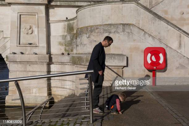 Next to a life buoy a father waits for his child to finish exploring the pavement on the riverside beneath Kingston Bridge on 7th November 2019 in...