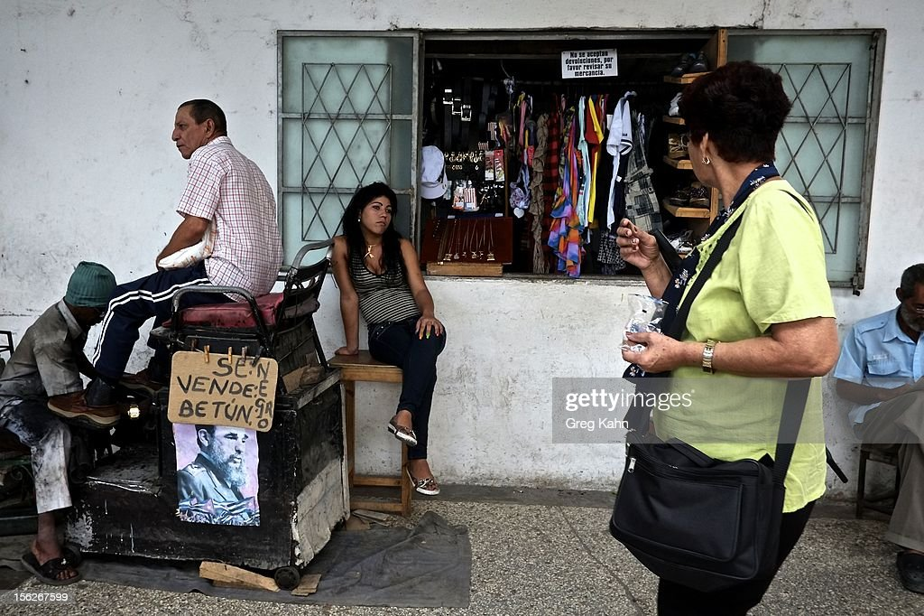Next to an old shoe shine business, a new independently owned store sells shirts and jewelry to shoppers in Old Havana on November 12, 2012 in Havana, Cuba. New business regulations in the communist country have allowed thousands of citizens to make money for themselves for the first time since 1959.